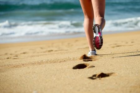 Woman running on beach  Sport footwear, sand footprints and legs close up  Runner feet detail  photo