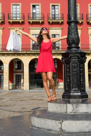 Joyful woman dancing after shopping in Spain   Successful fashion pretty girl raising white bags  Plaza Mayor of Gijon, Asturias, Spain  photo