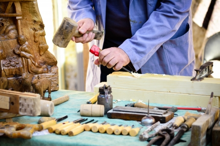 craftsmanship: Carpenter working and chiseling by hand in his old wooden workbench  Craftsmanship carving a block of wood