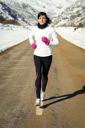 Woman running  in winter  Girl exercising on a mountain road on a snowy natural scenery  photo