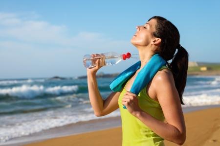 sudoracion: Fitness mujer aspersión de agua en su cuerpo y beber después de correr en la playa Mujer sudoración atleta y agotado después de hacer ejercicio