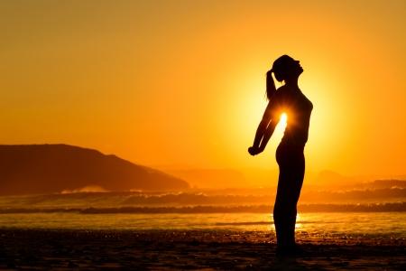 Fit donna facendo yoga e esercizi di respirazione rilassante sulla spiaggia al tramonto d'estate libertà, relax e armonia nella natura femminile che allunga le braccia da sola
