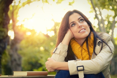 imagining: Pensive daydreaming woman relaxing in park on autumn  Female day dreamer using imagination outdoors  Stock Photo