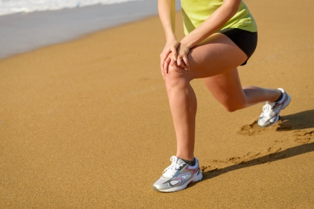 Fitness girl warming up and stretching before running in beach  Woman with running knee injury  photo