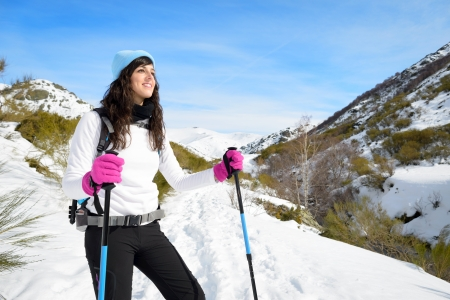 snow covered mountain: Woman hiking on sunny winter day in mountain landscape. Female hiker in warm outfit enjoying trail walk on snow covered track.