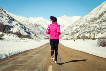 Woman running in cross country road on winter. Rear view of female runner training for marathon in snowy mountains landscape. photo