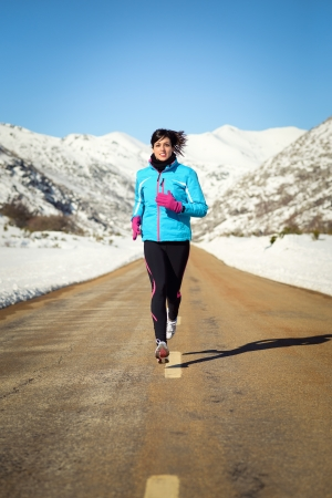 cold weather: Woman running fast in country winter mountain road. Female runner training endurance outdoor in cold weather. Stock Photo