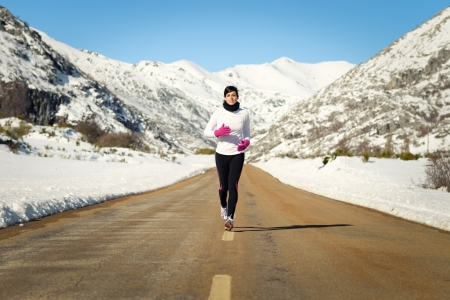 Female athlete running in cold winter mountain road. Woman training for marathon outdoors wearing warm sportswear. photo