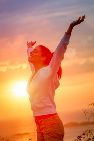 Woman enjoying freedom and life on beautiful and magical sunset. Blissful girl raising arms feeling free, relaxed and happy.