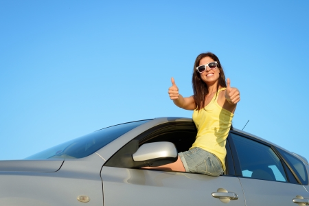 Female driver approving with thumbs up in summer roadtrip vacation. Car insurance, successful in driving license test or vehicle rental concept. photo