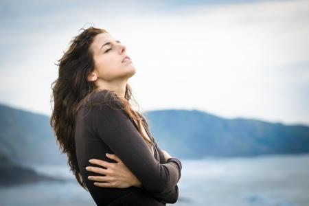 悲しい女震えと潮風を感じします。ノスタルジックな感情的な女性の彼女自身を抱き締める冷たい夏の終わりや秋の日に落ち込んで。美しい巻き毛