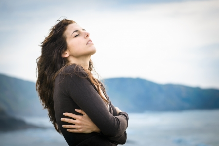 shivering: Sad woman shivering and feeling the sea breeze. Nostalgic and emotional female hugging herself and feeling low on cold late summer or autumn day. Beautiful curly hair caucasian model. Stock Photo
