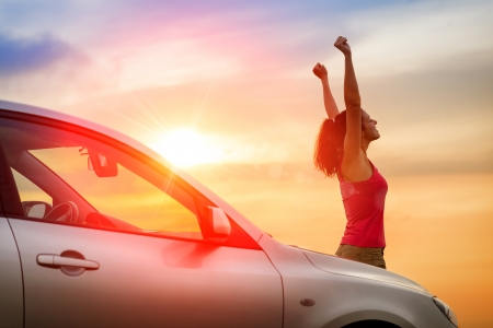 Female driver beside car raising arms and feeling the freedom of driving towards the sunset.  Woman and vehicle on beautiful sunshine background.