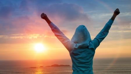 スポーツや生活の成果と成功の概念。背面ビューのスポーティな女の子美しい輝く太陽の光に向かって腕を上げます。