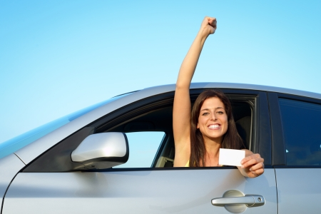 Female young driver in her car after passing the driving license test. Successful woman showing blank card in vehicle. Stock Photo