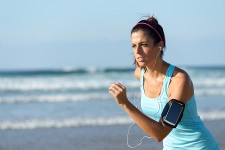 armband: Fitness donna in esecuzione sulla spiaggia mentre si ascolta la musica. Ragazza sportiva di indossare fascia di sport braccio per smartphone.