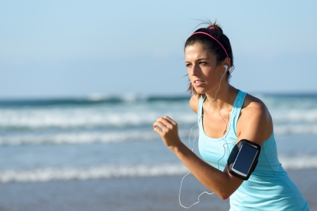 Fitness woman running on beach while listening music. Sporty girl wearing arm sport band for smartphone.