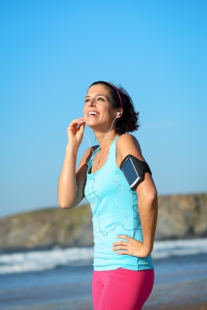 armband: Joyful fitness woman listening music on beach during a break from running. Sporty girl wearing arm sport band for smartphone and summer sportswear. Stock Photo