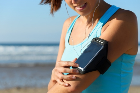 Sporty woman wearing arm sport band for phone or mp3 music player before running on beach. Female runner adjusting smarphone settings for exercising on summer outdoor.