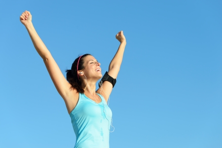 achiever: Fitness and exercising success. Sweaty woman listening music through earphones raising arms to clear blue sky. Successful sporty girl after training outdoor.