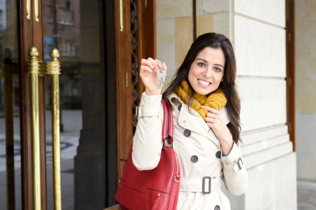 Cheerful woman holding home keys at apartment building entrance door outside. Happy and tranquil ownership, household insurance or rental concept. photo