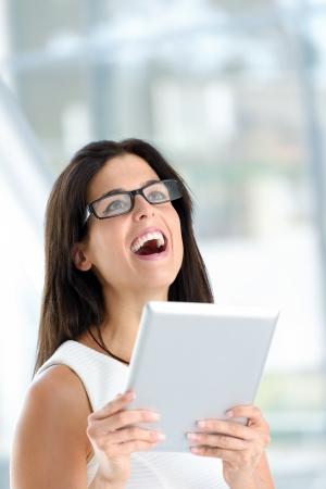 erfolgreiche frau: Erfolgreiche Frau mit digitalen Tablet. Gesch�ftsfrau mit Internet-Ger�t und l�chelnd. Beruflicher Erfolg Konzept. Lizenzfreie Bilder