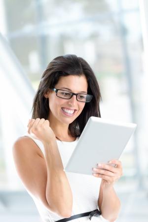 Femme réussie retenant la tablette digitale. Femme d'affaires en utilisant un dispositif Internet et souriant. Concept de la réussite professionnelle. Banque d'images
