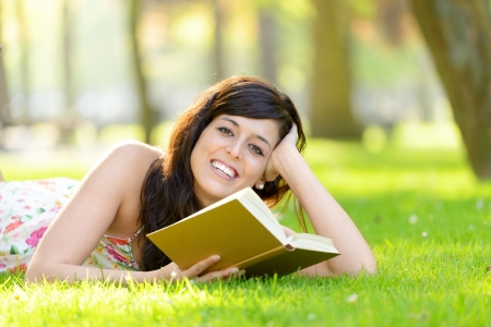 Happy woman reading book lying down on grass in park  Brunette beautiful girl relaxing and enjoying leisure on spring or summer outside