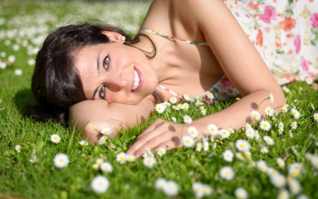 lying on grass: Happy woman resting and relaxing lying down on spring grass and flowers on park outdoors  Stock Photo