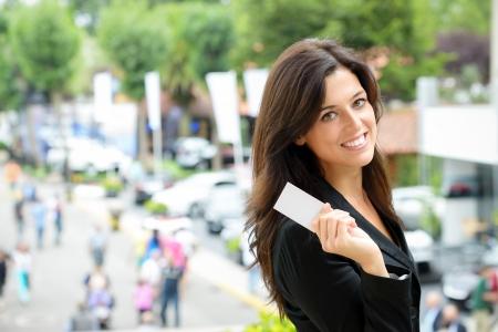 saleswoman: Successful female car sales representative showing business card  in automobile trade fair  Beautiful brunette saleswoman outdoor