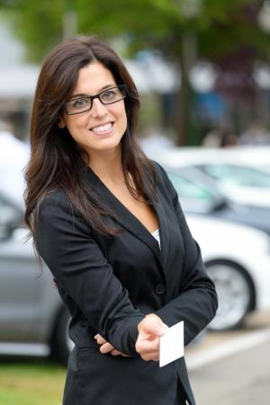 Erfolgreiche Frauen Auto Vertriebsmitarbeiter geben leere Visitenkarte in Luxus-Automobilmesse Schöne Brünette Verkäuferin Außen Standard-Bild - 25040363