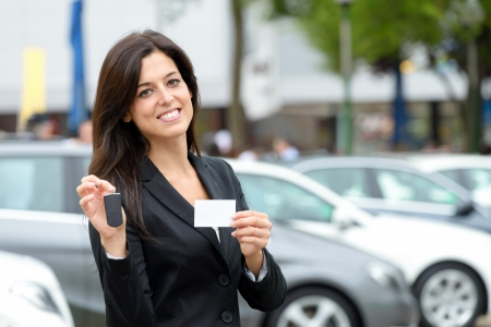 trader: Successful female luxury car sales representative showing car key and business card  in automobile trade fair  Beautiful brunette saleswoman outdoor
