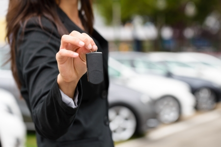 Saleswoman offering car key  Transport sales and rental concept  Stock Photo