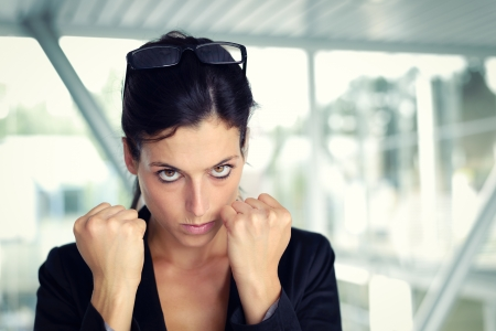 Upset and challenging businesswoman ready to fight  Female executive with furious eyes and raised fists  Stock Photo