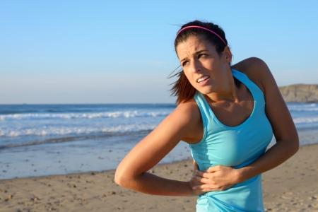 dolor muscular: Mujer de la aptitud con la cara de dolor de ri�ones mujer deportista con una lesi�n dolorosa o espasmo en los m�sculos serrato Foto de archivo