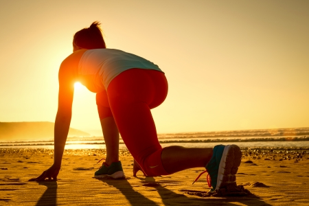 start position: Fitness woman ready for running at sunset or sunrise on beach  Female athlete in powerful starting line pose
