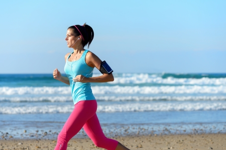 armband: Fitness woman on running workout at the beach on summer. Sporty girl wearing earphones and sport armband for listening smartphone music. Female healthy athlete training outdoors on sea background. Stock Photo
