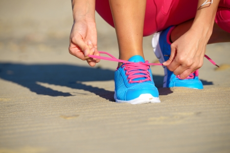 Female runner getting ready for running challenge workout on beach  Female athlete tying the laces of her sport shoes  photo