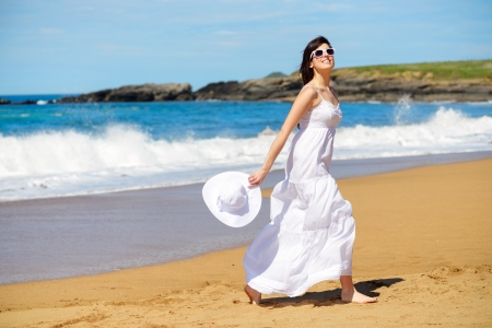 Playful woman on beach summer vacation dancing and having fun  Joyful girl on relaxing summertime walk  photo
