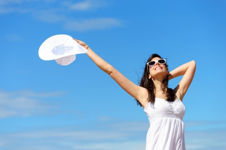 blissful: Happy woman enjoying freedom on summer   Blissful girl raising arms to the sky