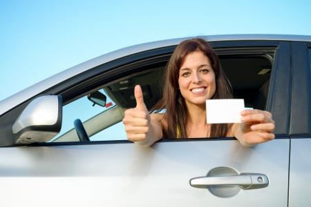 Vrouwelijke jonge automobilist ga duimen omhoog na het passeren van het rijexamen Succesvolle vrouw met blanco kaart en lachend in de auto