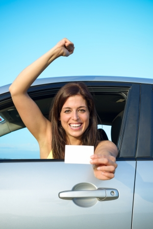 Female young car driver after passing the driving license test  Successful woman showing blank card and smiling in vehicle