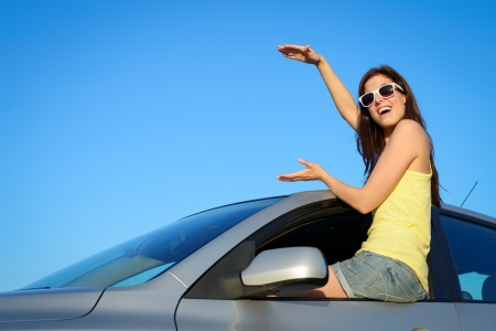 roadtrip: Female driver sitting on new car window holding virtual copy space for banner  Young woman on summer roadtrip  Driving license or vehicle rental concept
