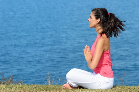 Woman doing yoga breathing and relaxing exercise by the sea  Relax and meditation concept  photo