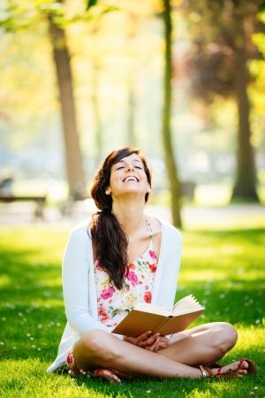 well read: Joyful woman reading fun book sitting on grass in park