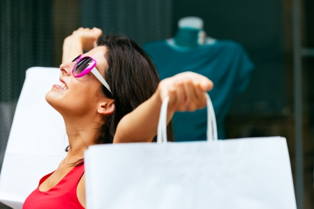 blissful: Blissful woman holding white shopping bags and enjoying the commercial store sales  Successful caucasian fashion brunette after buying clothes