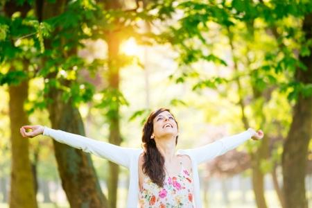 Mujer dichosa disfruta de la libertad y de la vida en el parque en la primavera Foto de archivo