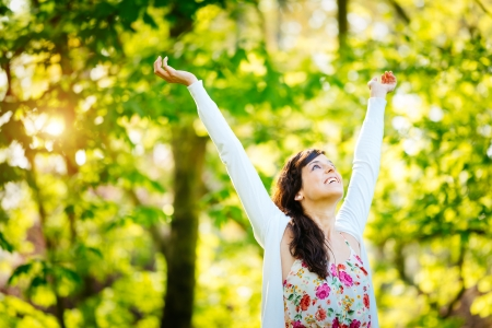arms  outstretched: Blissful woman enjoying freedom and happy life in park on spring