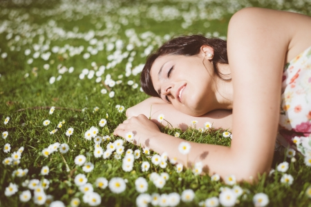 eye's closed: Happy woman resting and day dreaming lying down on grass and daisies in park outdoors  Beautiful girl with closed eyes in spring dress napping  Stock Photo