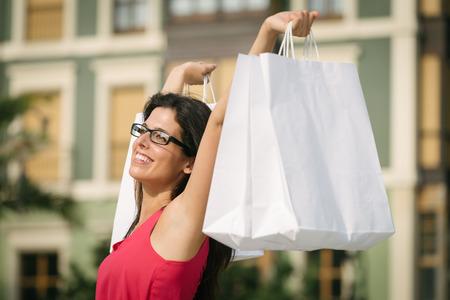 compras compulsivas: Mujer alegre levantar bolsas de la compra en blanco Exitosa comprador mujer que se divierten en la ciudad europea